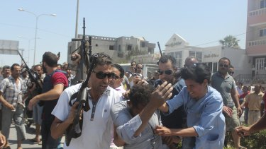 Police officers surround a man they suspect to be involved in opening fire on a beachside hotel in Sousse, Tunisia.