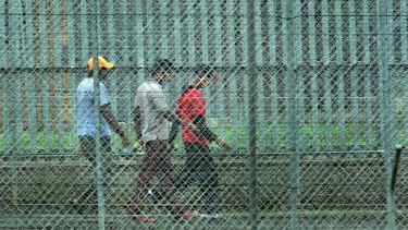 People walk behind the barbed wire fences at the Villawood Immigration Detention Centre in Sydney.