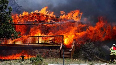 Where there's smoke ... a home is consumed by flames in Colorado in June when fires broke out in a record-breaking heatwave.