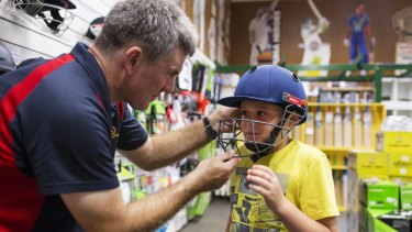 My size: Cooper Sullivan, 9, from Engadine, having his helmet fitted by Geoff Milliken from Kingsgrove Sports Centre.