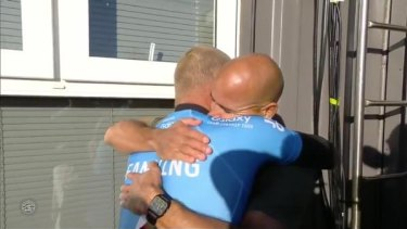 Mick Fanning and Kelly Slater hug after Fanning's close encounter with a shark.