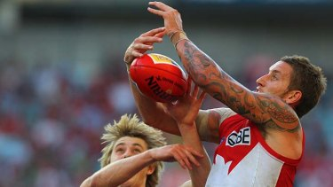 The big men fly . . . Swans firward Jesse White beats an Essendon player to the ball.