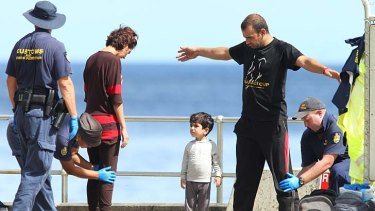 Seeking a new life: An Afghan family being checked after arriving at Christmas Island.