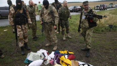 Pro-Russian separatists look at passengers' belongings at the crash site of Malaysia Airlines flight MH17.