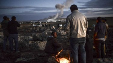 Kurdish people observe smoke rising from the Syrian town of Kobane, following an explosion as seen from the southeastern Turkish village of Mursitpinar.