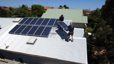Peter Allan helps Jarrod Tewierik from Harmonic Energy remove solar panels from Peter's house in Brunwick West.
