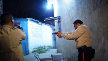 A special tactical division of the Sucre police force conduct a late night foot patrol in the Petare area of Caracas.