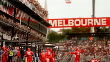 Spectators hang off the stands to watch as Michael Schumacher pulls into the pits for fuel at the 1997 Australian Grand Prix, Melbourne,