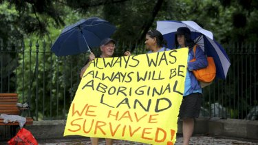 Jeff Gater from Acacia Ridge and Noritta Morseu-Diop, from Brisbane, hold up a sign as part of the Invasion Day protest on Australia Day.