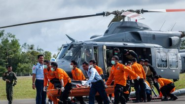 Members of Indonesian search and rescue team carry the body of a victim of the AirAsia flight QZ8501 crash at Iskandar Airbase.
