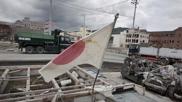 A Japanese flag flies over the remains of the town of Onagawa.