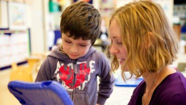 A teacher helps one of her preschoolers with digital storytelling.