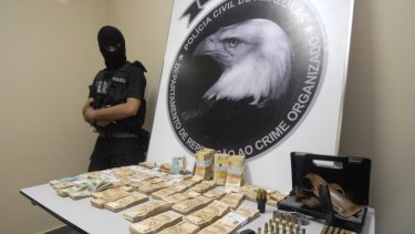 Brazil's police show arms, munitions and money allegedly confiscated from the home of legislator and television show host Wallace Souza, inset.