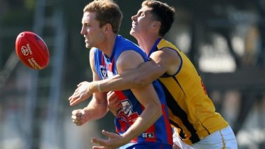 Sam Pleming of Port Melbourne handballs as he is tackled by Lewis Pierce of Sandringham.