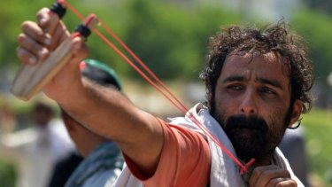 A protester fires a slingshot towards riot police during clashes in the Pakistani capital.