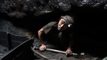 Gilla Rai, 15, emerges from the rat-hole where he has been mining coal, in Meghalaya in north-east India.