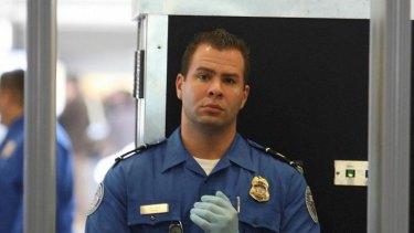 A TSA agent waits for passengers to walk through a detector.