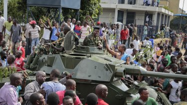 Demonstrators celebrate what they perceive to be an attempted military coup d'etat, with army soldiers riding in an armored vehicle in the capital Bujumbura, Burundi.