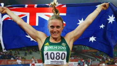 Sally Pearson of Australia celebrates after crossing the finish line first.
