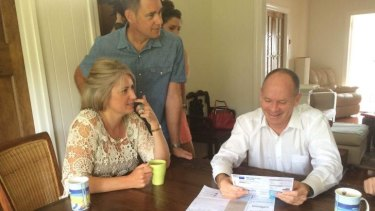 Gordon Park couple Amy Ward and Todd Winks go over their power bills with Premier Lord Mayor Campbell Newman on Sunday morning.