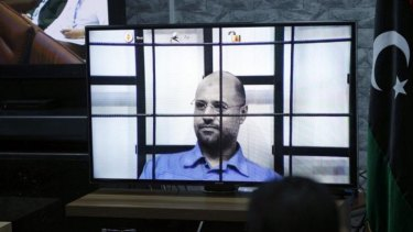 Saif al-Islam Gaddafi on a screen via video link in a Tripoli court.