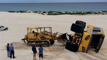 A bulldozer is called in to retrieve the four-wheel-drive after it rolled over in a dune crash.