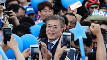 South Korean presidential candidate Moon Jae-in of the Democratic Party is surrounded by his supporters upon his arrival for an election campaign in Gwangju, South Korea.