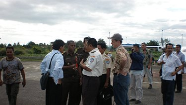 Not so fast ... immigration officials bicker with Yafeth Bonai, second from left, on the runway at Merauke airport yesterday.