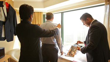 Suits you … Martin Raja, left, and Harry Menon from Raja Fashions of Hong Kong take the measurements of a Sydney client at the Pullman hotel near Hyde Park.