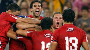 Flying high ... jubilant Reds players react after their stirring win over the Bulls in Brisbane.