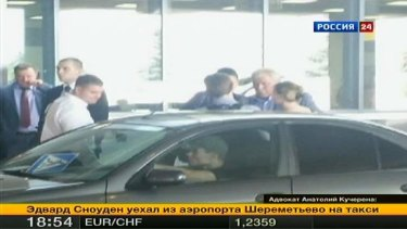 Fugitive former U.S. spy agency contractor Edward Snowden (centre) talks with Russian lawyer Anatoly Kucherena (second right) in front of a car at Moscow's Sheremetyevo airport.