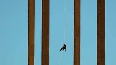 """The """"ex-military'"""" protester abseils down after staging his Harbour Bridge protest."""