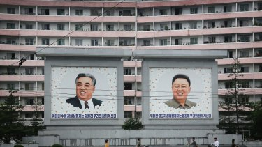 North Koreans are dwarfed by giant portraits of the late North Korean leaders Kim Il Sung and Kim Jong Il in Wonsan, North Korea.
