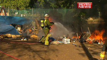 A firefighter hoses down flames at the Musgrave Park Aboriginal Tent Embassy.