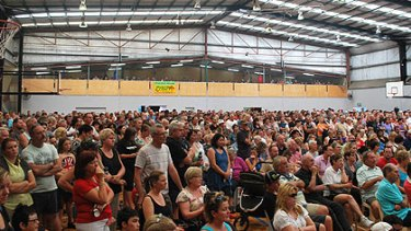 A crowd of hundreds gathers for an emergency meeting at the Armadale Arena evacuation centre.