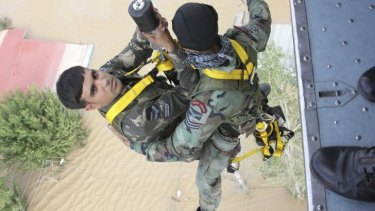 Member of the Indian Air Force's Garud Commando Force are lowered from a helicopter during a rescue operation for flood-affected people stranded on rooftops in Srinagar.