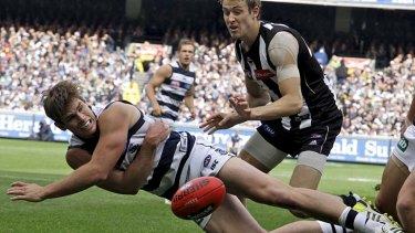 Going down swinging: Geelong's Tom Hawkins tries to tap the ball back into play.