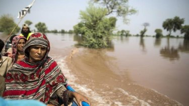 A flood victim sits on a boat while being evacuated from her flooded house following heavy rain in Jhang, Punjab province.