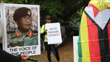 People hold their messages in Harare to demonstrate for the ouster of President Robert Mugabe.