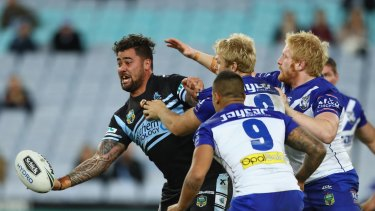 Andrew Fifita of the Sharks passes as he is tackled.