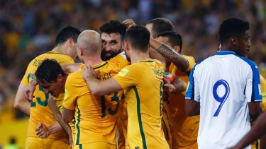 Job done: Mile Jedinak is mobbed after scoring.