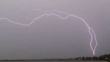 Lightning seems to threaten a plane and the BHP tower.