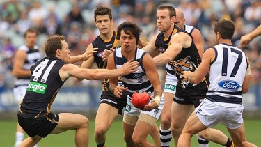 In trouble: Allen Christensen tries to get the ball to a Geelong teammate.