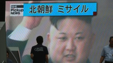 People walk in front of a TV image of North Korean leader Kim Jong-un shown on a large screen after a missile landed in the waters of Japan's economic zone.