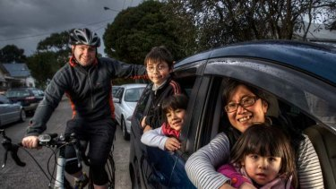 Damian Walsh cycles to work while Junko Kobayashi drives with their children (left to right) Declan, Grace and Gabbi.