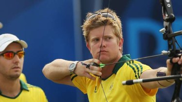 Mat Masonwells prepares to shoot as team mates Matthew Grey and Taylor Worth of Australia look on.