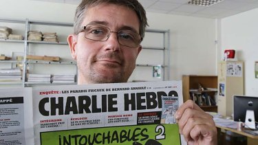 Publishing director of the satiric weekly Charlie Hebdo, Charb, displays the front page of the magazine in Paris.