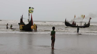 A boy watches fishing boats leave from the southern coast of Bangladesh. Rohingya are, increasing numbers, boarding people smugglers' boats like these, and meeting up with cargo ships further out to sea, which take them to Thailand, Malaysia, and Indonesia.