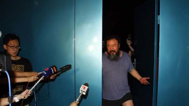 Considerably thinner ... Chinese artist Ai Weiwei waves from his studio after being released by Chinese police from prison, where he was kept for 81 days. Ai was detained at Beijing Airport on April 3.