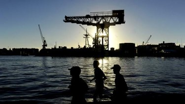 Joggers run past the hammerhead crane on Garden Island in Sydney